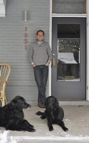 Patrick Quinlan at home in the Park Hill neighborhood on the front porch with his dogs, Jasmine and Parma.