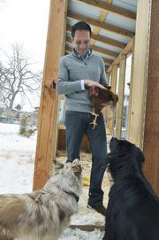 Patrick Quinlan at home with the dogs and chickens of which there are three dogs and 7 chickens.