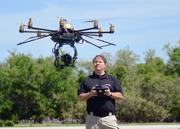 Al Ducharme of Hoverfly operates the camera on an Erista model drone flyer over a field by the company headquarters.