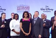 First Lady Michelle Obama joins Disney Chairman and CEO Bob Iger onstage with a group of Disney cast members, who are also veterans, during the 2013 Disney Veterans Institute workshop in the Boardwalk Hotel convention center Walt Disney World resort.
