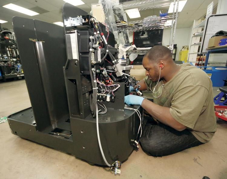 Lewis Pace III works on the drive train of a GT10 automated guided vehicle at Seegrid Corp.