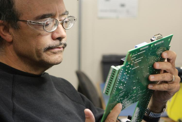 Rob Verone tests a printed circuit board used in MSA's Chillgard monitor, a wall-mounted system used to detect refrigerant leaks in industrial environments.