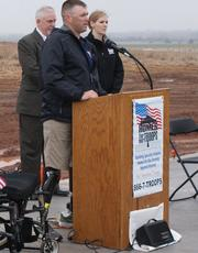 """Marine Sgt. James """"Matt"""" Amos speaks Saturday to the many people gathered for the event. Behind him, from left, are Larry Gill, veterans' liaison for Homes for Our Troops, and Autumn Oster, community outreach coordinator for Homes for Our Troops."""