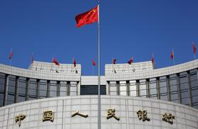A Chinese flag flies outside the People's Bank of China (PBOC) headquarters stands in Beijing, China, on Monday, March 4, 2013.