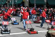 A group of lawnmower enthusiasts walk in the parade.