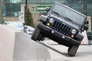 The Chrysler Group LLC Jeep Rubicon vehicle drives through the company's trail ride set up outside the event.