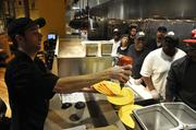 Employees watch as a cook demonstrates a dish at Tupelo Honey.