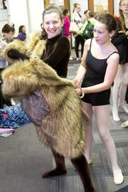 Taryn Huffman, left, gets help into her mouse costume from Leah Wicks as they ready for rehearsal.