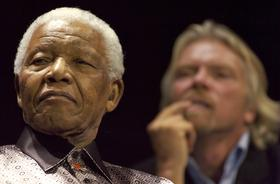 Former South African President Nelson Mandela, left, shown here with  U.K. billionaire Richard Branson listen to Peter Gabriel sing