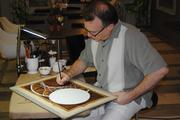 Coffee artist Steven Mikel works on some pieces he will hang around the hotel.