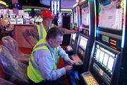 Workers put the finishing touches on the slot machines.