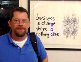 Artist Hugh MacLeod in front of 'Business is change'