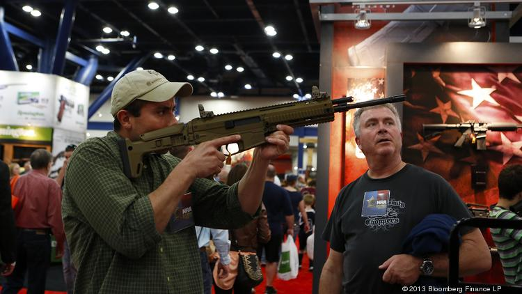 An attendee looks through the scope of a Freedom Group Inc. Bushmaster brand assault rifle during the 2013 National Rifle Association (NRA) Annual Meetings & Exhibits.