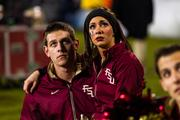 Florida State cheerleaders look somberly at the video board while an injured player is assisted on the field.