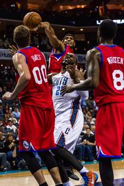 Charlotte Bobcats center Al Jefferson has the odds firmly against him as he goes for a loose ball against Philadelphia 76ers defenders including Spencer Hawes and Tony Wroten.