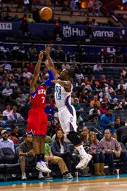 Philadelphia 76ers guard Lorenzo Brown fires a three-point attempt over Charlotte Bobcats defender Kemba Walker.