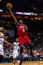 Philadelphia 76ers guard James Anderson drives for a layup as Charlotte Bobcats defenders Josh McRoberts and Ramon Sessions trail.
