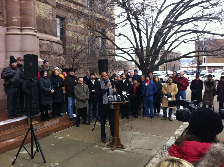 Flanked by supporters, Rob Richardson speaks about the Cincinnati streetcar project outside City Hall on Monday.