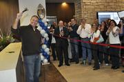 Rob Cohen, CEO of IMA, calls up unsuspecting employees to help cut the ribbon introducing their new space.