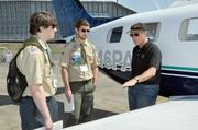 Alaska Air Group Chairman Bill Ayer, at right, talks with two Boy Scouts who are getting their badges in aviation, encouraging them to consider careers in the industry. Ayer stands in front of his own airplane for the discussion on Alaska Airlines-sponsored Aviation Day in 2012.