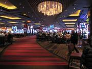 A gaming floor has slots (seen at left) and craps tables at right.
