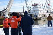 Members of the Stephen L. Colby Response Unified Command observe the lifting and refloating of the 154-foot towboat near LeClaire, Iowa, on Monday. Crews have worked continuously to repair and refloat the vessel since it reportedly struck an unknown submerged object in the Mississippi River channel and sank Nov. 25.