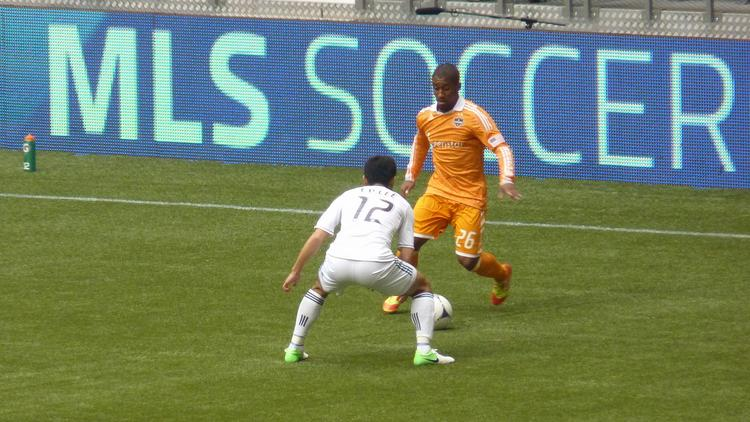 Players converge on the ball during an MLS match between the Houston Dynamo and Vancouver Whitecaps.