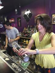 James Agency PR Director Angie Miller practices a pouring technique as Creative Director Shane Tang stands by during a team-building event at the Bartending Academy in Tempe.