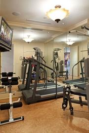 The condo has a mirrored fitness room with cork floor.
