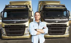 Actor Jean-Claude Van Dam poses in front of two Volvo Trucks.