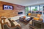 Another view of the Resident Lounge features flat screen TV, comfortable seating and a view toward the pool.