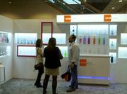 Several DSTILL conference attendees chat in the booth hosted by Saver Glass, a French bottle-making company.