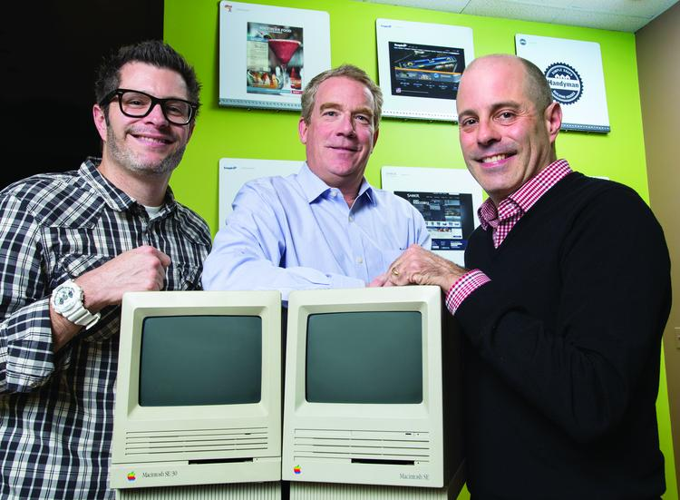The new leadership team for Sales Factory + Woodbine following the merger of Triad marketing firms The Sales Factory and Woodbine. Pictured here, from left, are Chief Creative Officer Matt King, President Peter Mitchell and CEO Ged King. The trio are standing with early model Macintosh computers each firm used when they launched in the 1980s.