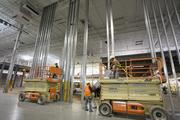 Herbalife Ltd. and other major manufacturers and distributors expanding in the Triad are increasingly seeking facilities with ceiling heights that can reach 40 feet or higher to accommodate equipment such as sophisticated racking systems. Pictured here are construction workers at Herbalife's new facility in Winston-Salem, where the company will leverage equipment that reaches three stories high.