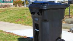 The new trash cans handed out by the city can be dragged to a garbage truck, which has equipment that hoists the contents into the truck so workers don't have to lift it themselves.
