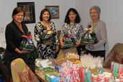 From left, Rebecca Siu-Rodriguez, Carol Maunakea, Cathy Crowley, and Valerie Correa of Hawaiian Telcom pose with gift bags filled with donated personal items for the Child & Family Service Gerontology Program, which provides help for Hawaii's older adults and their caregivers on Oahu.