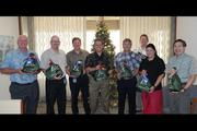 The Hawaiian Telcom team, from left, Kevin Paul, Scott Barber, Paul Krueger, Eric Yeaman, John Komeiji, Steve Golden, Amy Aapala, and Francis Mukai, pose with gift bags filled with donated personal items for the Child & Family Service Gerontology Program, which provides help for Hawaii's older adults and their caregivers on Oahu.
