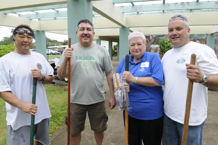 From left, Damien Kim, business manager with IBEW Local No. 1186; Randy Perreira, executive director of the Hawaii Government Employees Association; Joan Husted, retired executve director of the Hawaii State Teachers Association; and James Wataru, state president for the United Public Workers Hawaii, participate in the first  Labor of Love, a union give-back project at Waimanalo Elementary and Intermediate School.