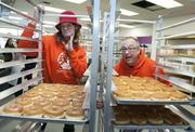 """Tres Shannon Kenneth """"Cat Daddy"""" Pogson, of Voodoo Doughnut, with the first batch of doughnuts in their Denver store."""