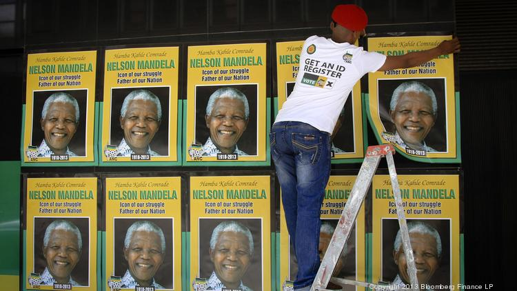 An African National Congress (ANC) employee attaches posters to the outside of the political party's headquarters following the announcement of the death of the former South African President Nelson Mandela in Johannesburg, South Africa, on Dec. 6. Mandela, the freedom fighter who emerged from 27 years in prison to become South Africa's first elected black president and a global symbol of reconciliation, died at his home in Houghton aged 95.