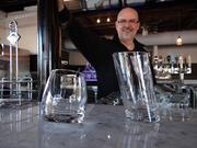 "Stephen Marino, Mad Hatter's general manager, showcases the restaurant's signature glasses: the rock 'n roll tumbler glass —which spins in a circle rather than sitting flat on the table — and the ""Pisa"" glass, named for the world wonder that leans over just a little too far."