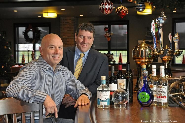 From left, C.J. DeCrescente Jr., president and CEO of DeCrescente Distributing Co. Inc., with Frank Crisafulli, in charge of the company's newly added wine-and-liquor business. The two are seated at the company's in-house bar in Mechanicville, NY, with some of the new product line.
