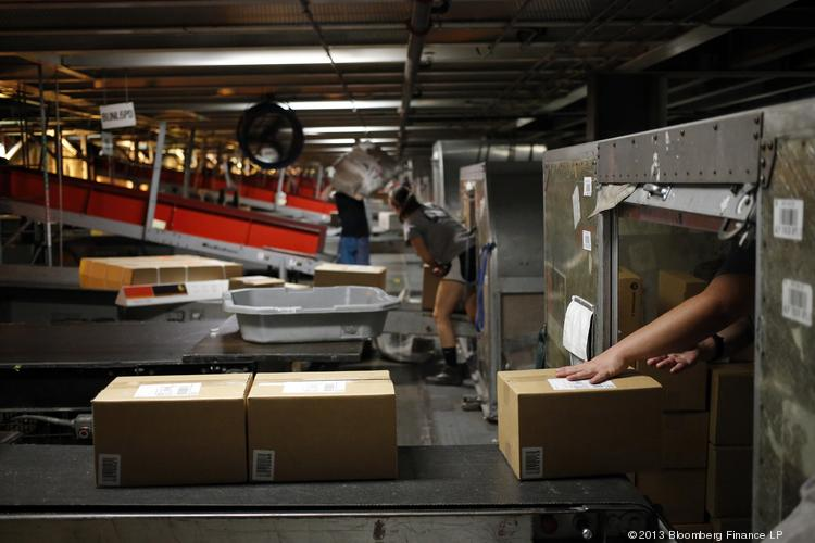 A package handler unloads incoming boxes during United Parcel Service Inc.'s Worldport overnight shipping operations at Louisville International Airport.