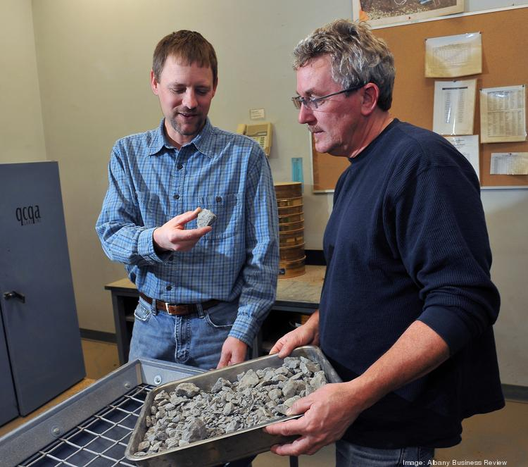 From left, Tod Kobik and Will Stanton examine samples of crushed stone. They are buying QCQA, which is a division of TransTech Systems Inc., of Schenectady. The sale price was not disclosed.