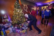 Attendees drop off their donated toys at a Christmas tree.