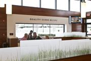 The seating area is partitioned by panels of frosted glass with stenciled grass.