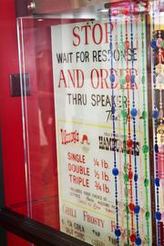 A hand-painted sign from the second restaurant in the chain shows Wendy's was an early innovator in drive-throughs. The beads divided areas in early restaurants.