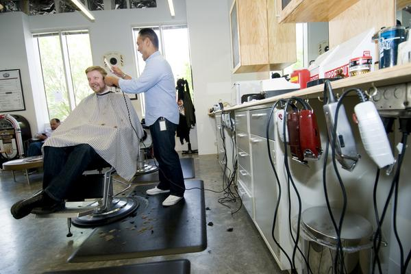 #11: Onsite barbershop:  Barber Anthony Camacha cuts Luke Sanwich's hair at Facebook's onsite barbershop. There are multiple stations at the barbershop, and employees can make a reservation using a digital system.