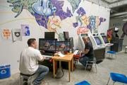 #12: A classic video arcade:  Two employees battle one another over their lunch break in the arcade. Traditional arcade games sit next to serious gaming rigs at the arcade. Hanging above the arcade is a stuffed hammerhead shark.