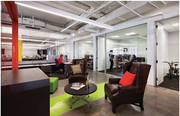 Small neighborhoods of workstations, glass-fronted offices and informal collaboration areas.